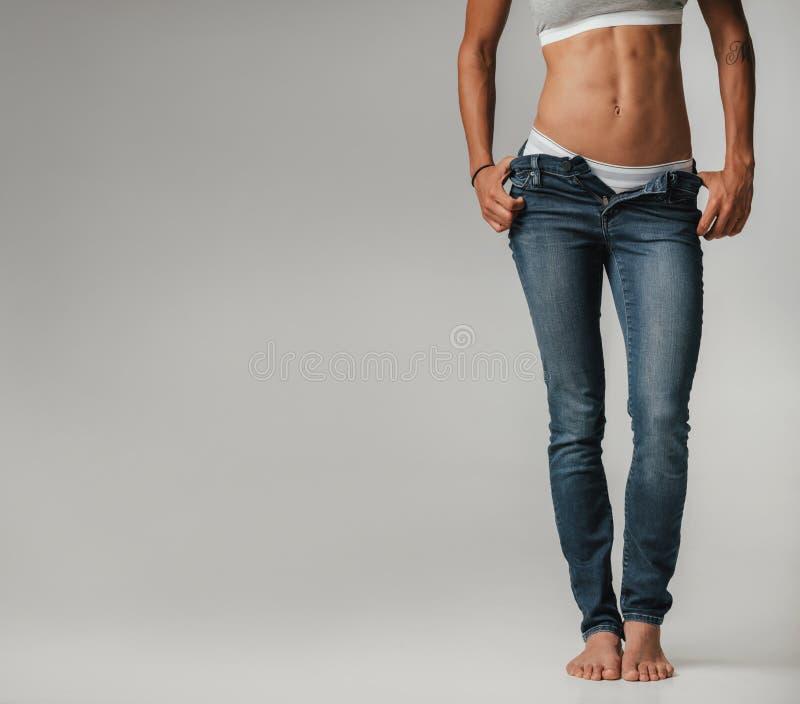 Seksowna stonowana młoda kobieta pozuje z unzipped cajgami zdjęcie stock
