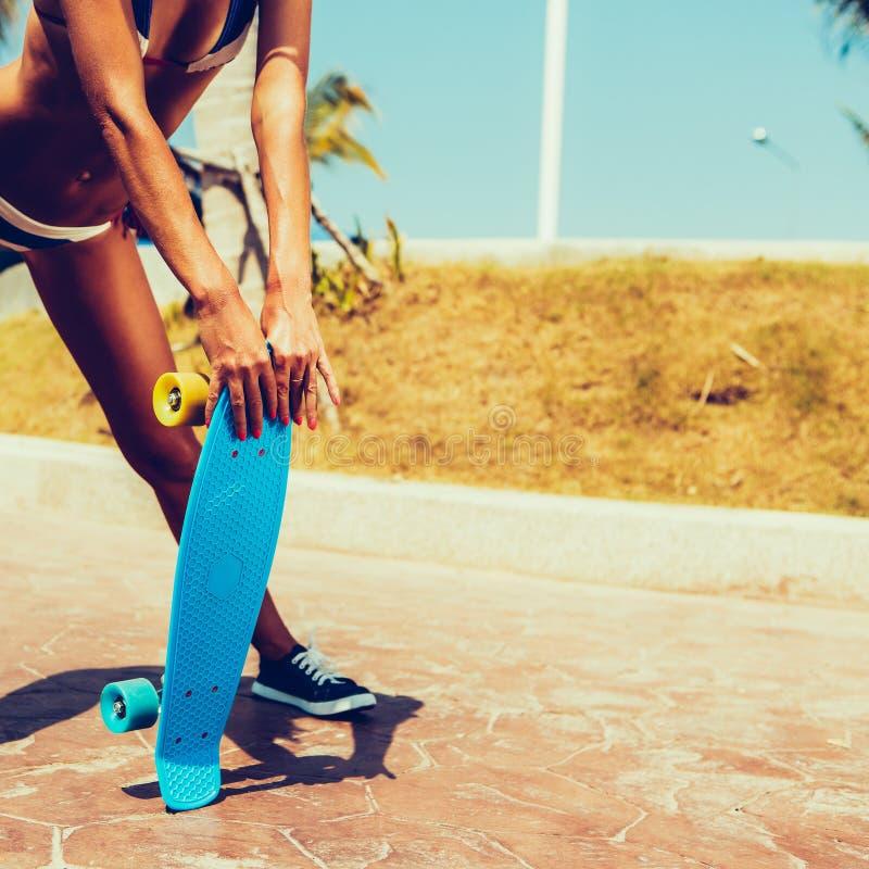 Seksowna suntanned dama zostaje z błękitną cent deską na streat fotografia royalty free