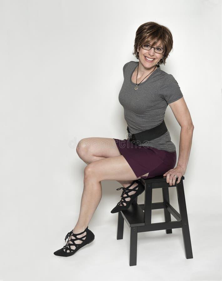 Seksowna, szczupła w średnim wieku kobieta na krok stolec, zdjęcia stock
