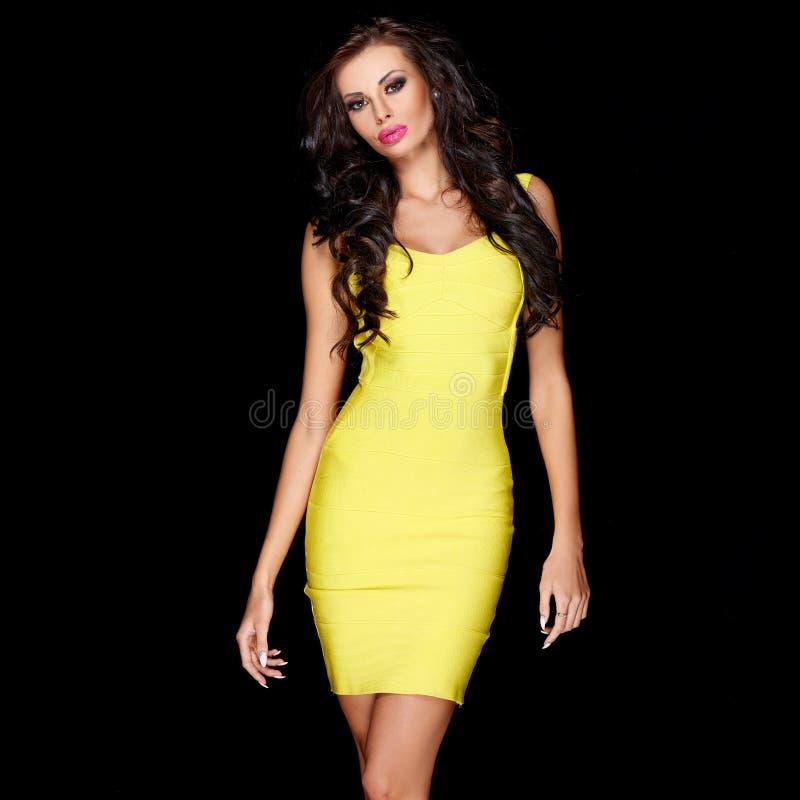 Seksowna szczupła brunetka pozuje w kolor żółty sukni obraz royalty free