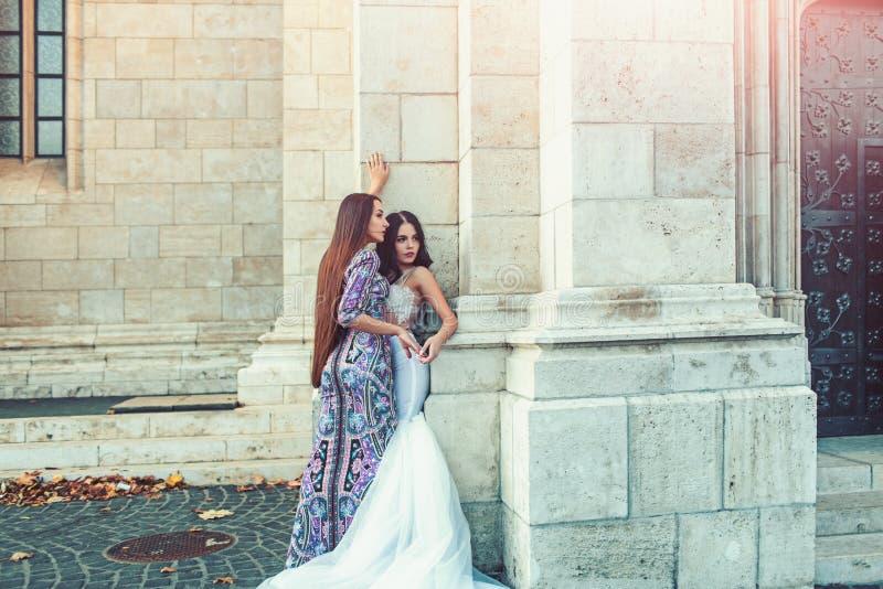 Seksowne dziewczyny w sukni z eleganckim włosy seksowna dziewczyny poza przy kamienną kolumną w ślubie i moda ubieramy fotografia stock