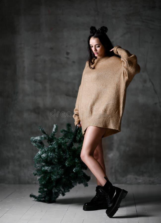 Seksownego modniś kobiety chwyta Bożenarodzeniowy jedlinowy drzewo w trykotowej pulower bluzce gotowej dla nowego roku świętowani obrazy royalty free