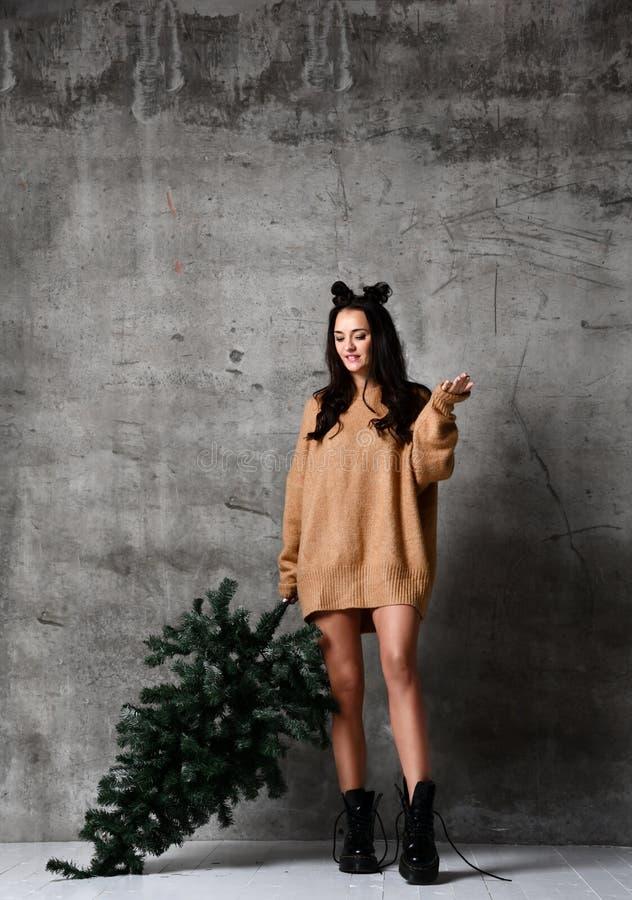 Seksownego modniś kobiety chwyta Bożenarodzeniowy jedlinowy drzewo w trykotowej pulower bluzce gotowej dla nowego roku świętowani fotografia royalty free