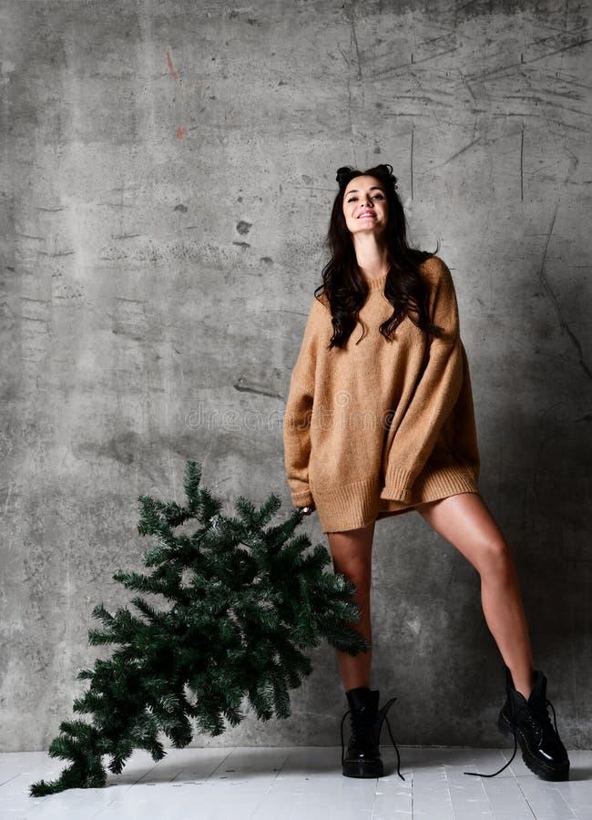 Seksownego modniś kobiety chwyta Bożenarodzeniowy jedlinowy drzewo w trykotowej pulower bluzce gotowej dla nowego roku świętowani obraz stock