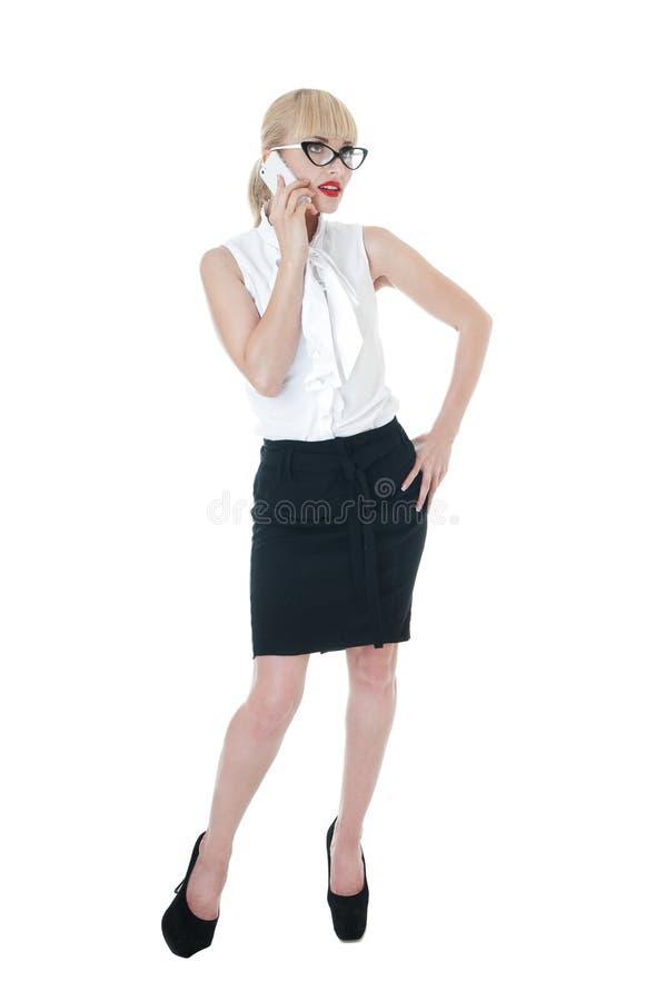 Seksownej blondynki biznesowa kobieta używa smartphone jest ubranym szkła. zdjęcia stock