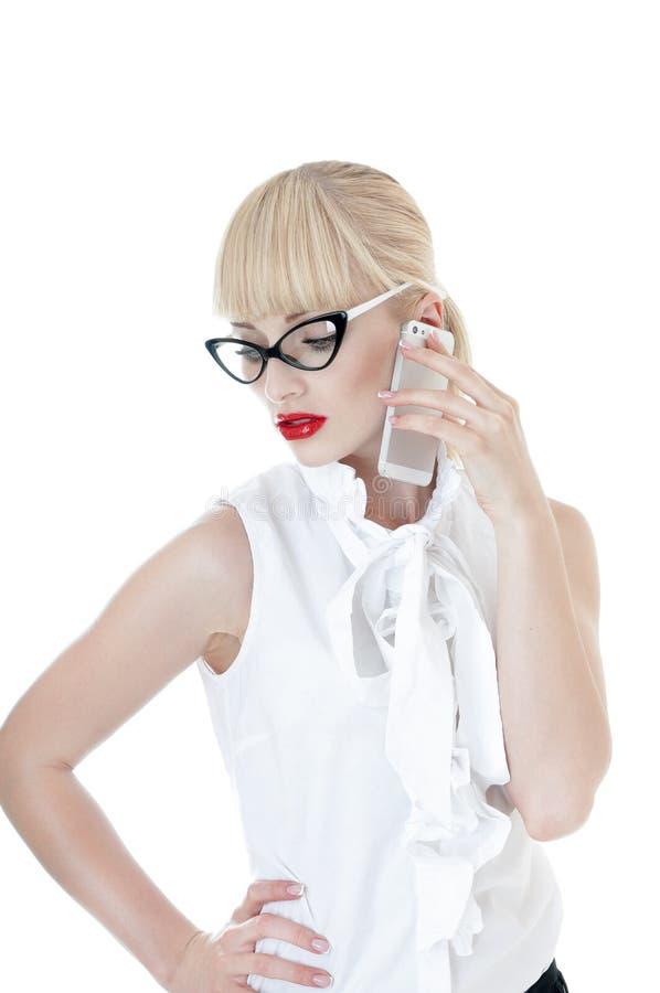Seksownej blondynki biznesowa kobieta używa smartphone jest ubranym szkła. obrazy royalty free