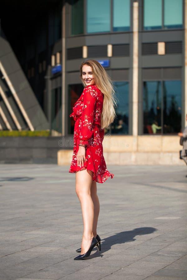 Seksownej blondynki wzorcowy pozować na th ulicie w czerwonej lato sukni zdjęcie royalty free