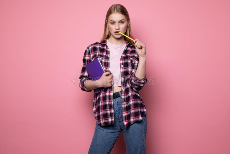 Seksownej pi?knej blondynki ?e?ski ucze? w przypadkowych ubraniach z purpurowym notatnikiem w r?ce i ? obrazy stock