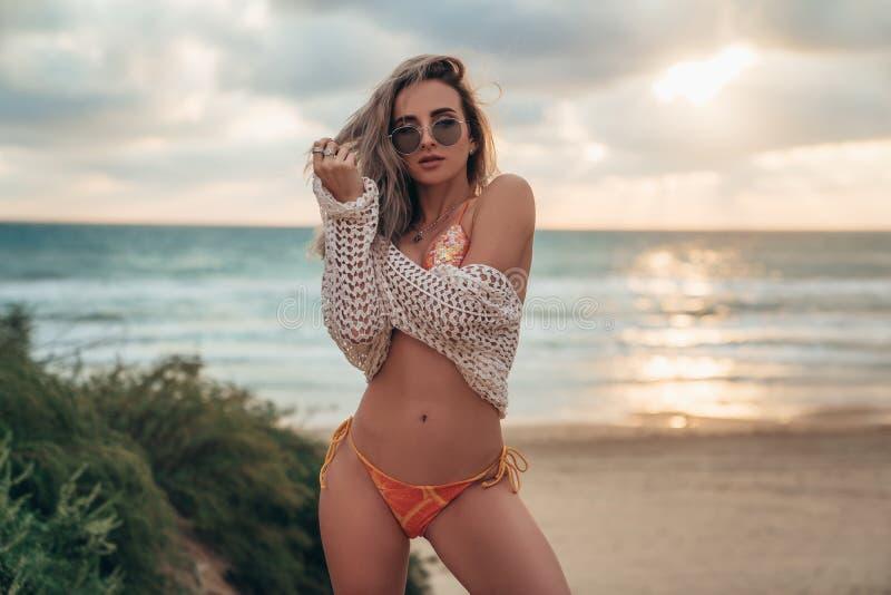 Seksownej z włosami blondynki wzorcowi jest ubranym okulary przeciwsłoneczni, swimsuit i tunika, pozują na plaży przegapia ocean fotografia royalty free