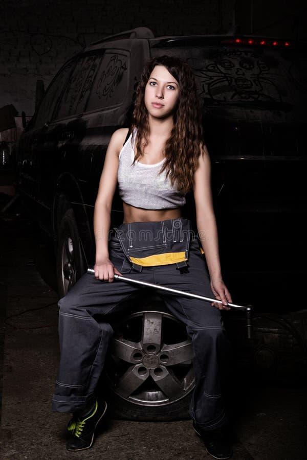 Seksowny dziewczyna mechanika obsiadanie na oponie trzyma wyrwanie w jego ręce bezbarwny życia pojęcie zdjęcie stock