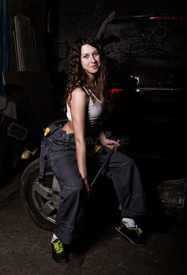 Seksowny dziewczyna mechanika obsiadanie na oponie trzyma wyrwanie w jego ręce bezbarwny życia pojęcie zdjęcie royalty free