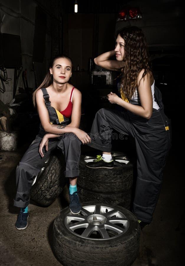 Seksowny dziewczyna mechanika obsiadanie na oponie trzyma wyrwanie w jego ręce na samochodowe naprawy bezbarwny życia pojęcie zdjęcia royalty free