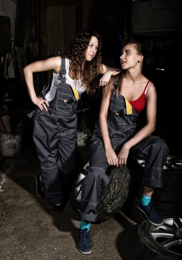 Seksowny dziewczyna mechanika obsiadanie na oponie trzyma wyrwanie w jego ręce na samochodowe naprawy bezbarwny życia pojęcie obrazy royalty free
