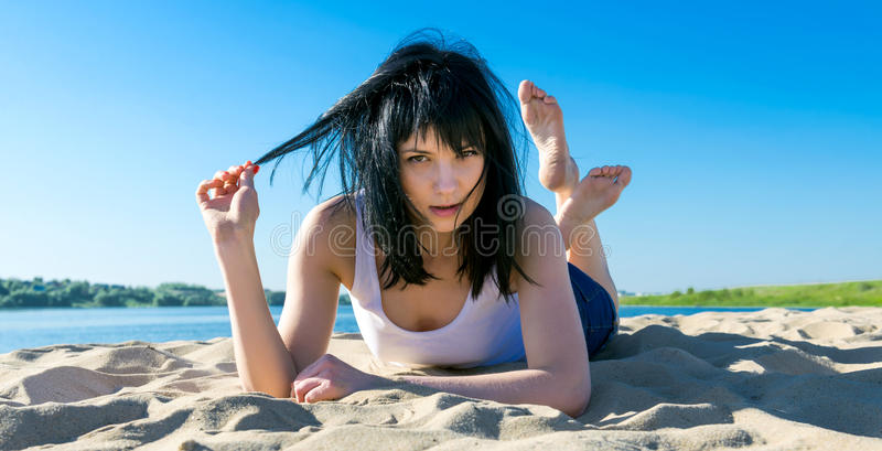 Seksowny kobiety lying on the beach na piaskowatej plaży przy latem zdjęcie stock