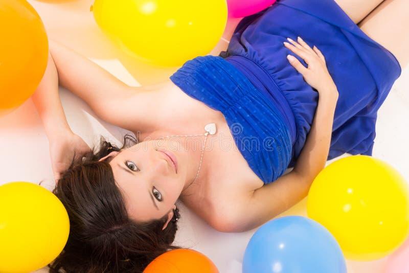 Seksowny młodej kobiety lying on the beach na podłoga wśród balonów zdjęcia stock