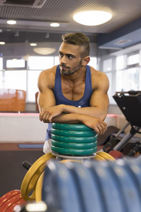 Seksowny młody człowiek ma odpoczynek po trenować w gym fotografia stock