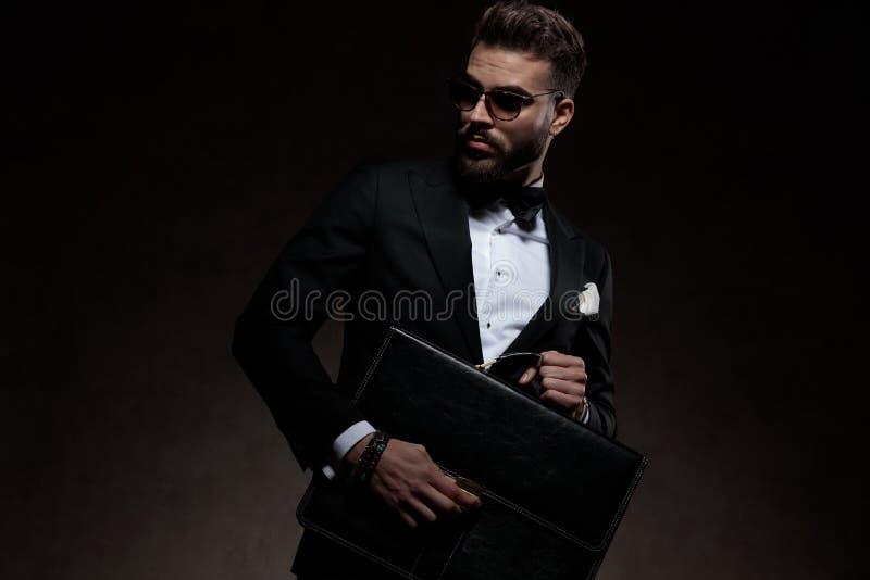 Seksowny młody elegancki mężczyzna w smokingu trzyma teczkę i otwiera obrazy royalty free