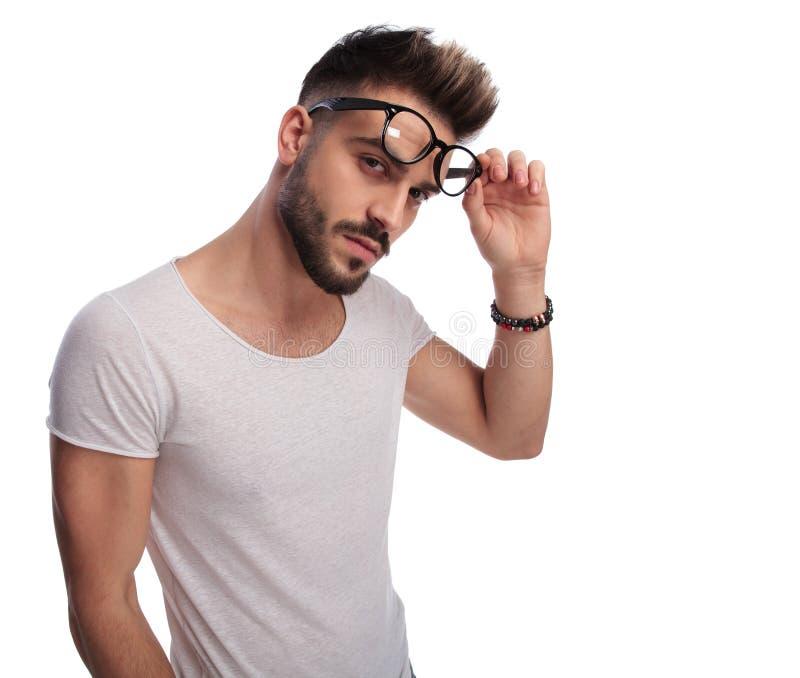 Seksowny młody przypadkowy mężczyzna usuwa jego szkła zdjęcia stock