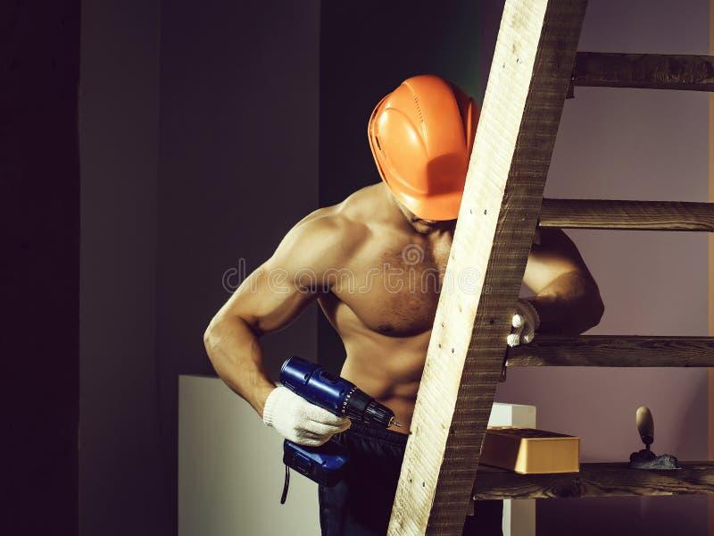 Seksowny mięśniowy mężczyzny budowniczy na drabinie fotografia royalty free