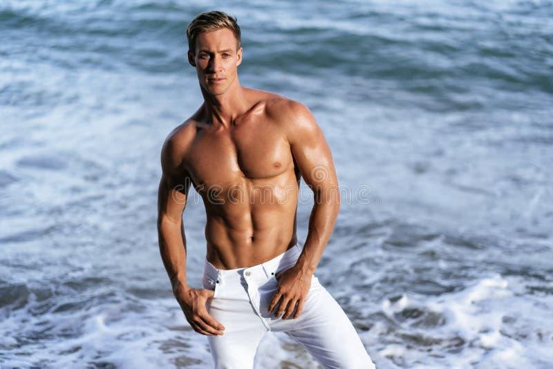 Seksowny mięśniowy facet w biel spodniach i bez koszuli pozować na tropikalnej piaskowatej plaży, ocean fale przy tłem obrazy stock