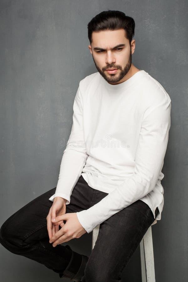 Seksowny moda mężczyzna model w biały puloweru, cajgów i butów pozować dramatyczny, zdjęcie royalty free