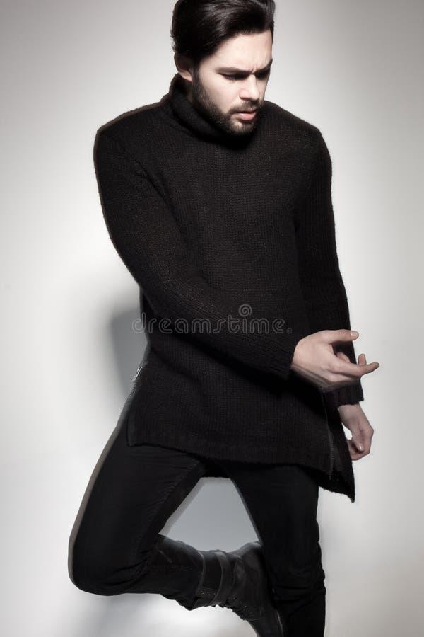 Seksowny moda mężczyzna model w czarny puloweru, cajgów i butów pozować dramatyczny, zdjęcie royalty free
