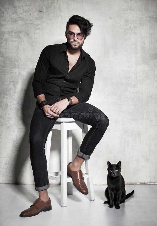 Seksowny model ubieram moda mężczyzna przypadkowy pozować z kotem przeciw grunge ścianie zdjęcie stock
