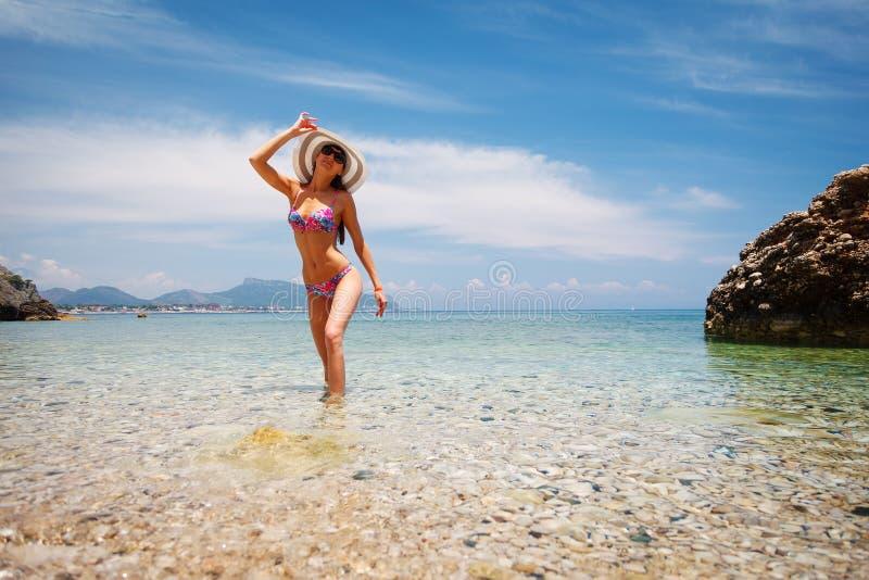 Seksowny plecy piękna kobieta w bikini, kreatywnie kapeluszu i okularach przeciwsłonecznych na dennym tle, r obraz royalty free