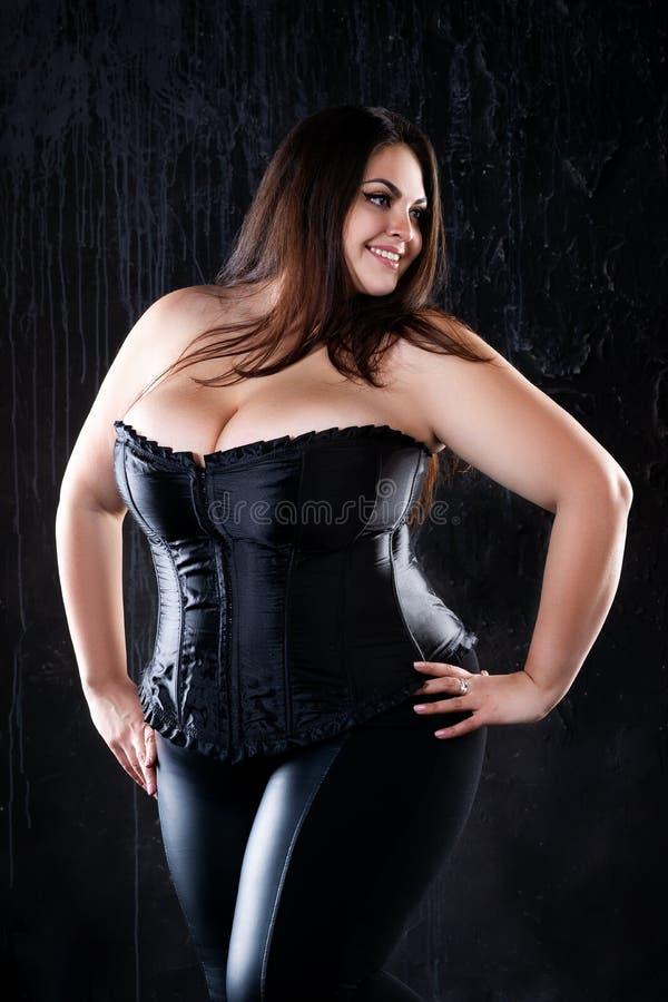 Seksowny plus rozmiaru model w czarnym gorseciku, gruba kobieta z dużymi naturalnymi piersiami na ciemnym tle, ciało pozytywu poj zdjęcie royalty free