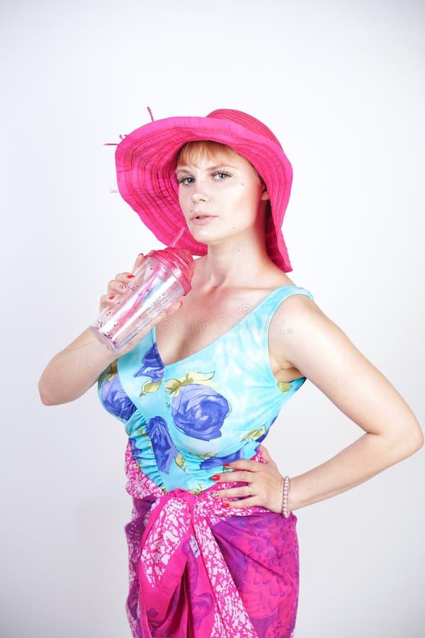 Seksowny plus wielkościowa dziewczyna w błękitnym swimsuit w pareo modnych jaskrawych stojakach na białym tle w Stu i, fuksja kap zdjęcia royalty free