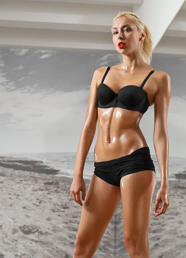 Seksowny, sportowy przeciw tłu, blondynki kobieta w gym, zdjęcie royalty free