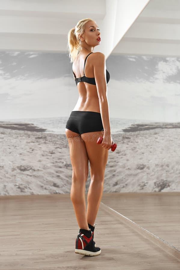 Seksowny, sportowy przeciw tłu, blondynki kobieta w gym, obraz royalty free