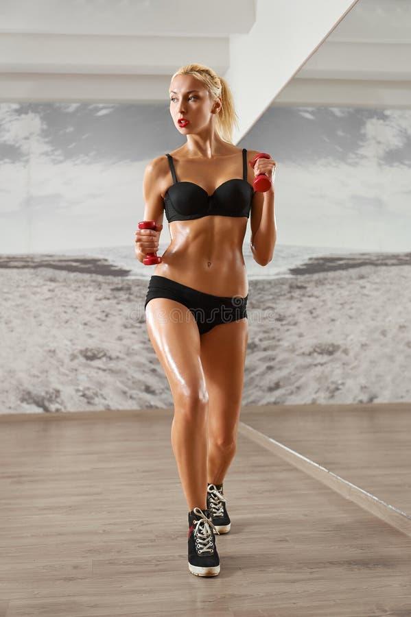 Seksowny, sportowy przeciw tłu, blondynki kobieta w gym, zdjęcia royalty free