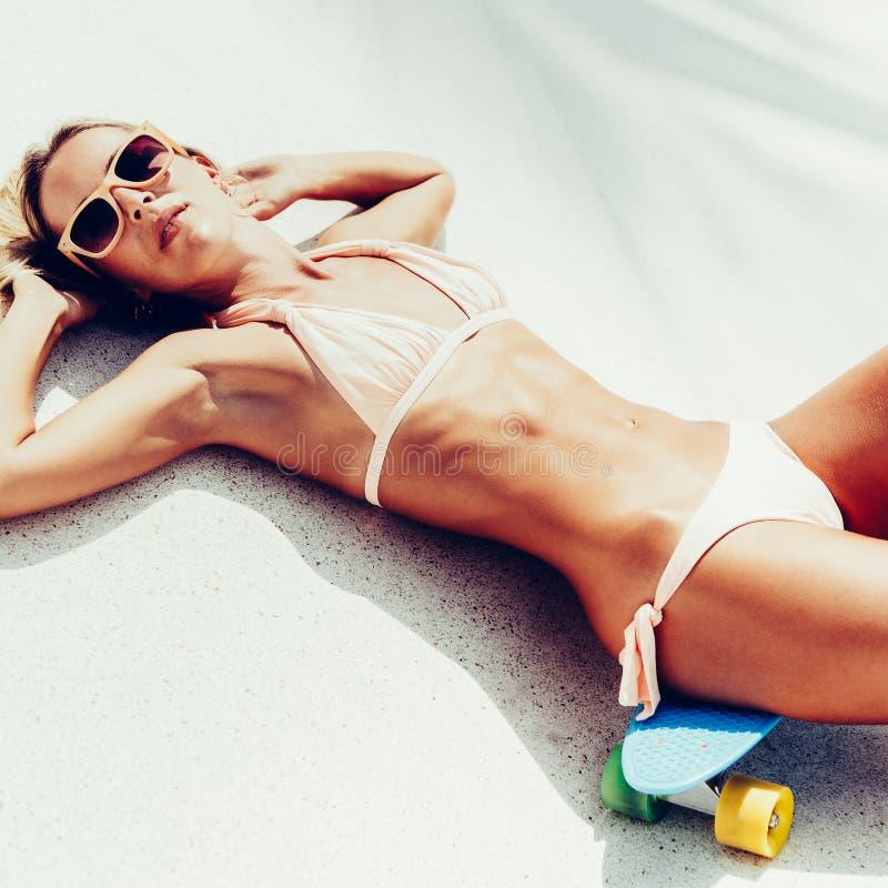 Seksowny suntanned damy lying on the beach na błękitnej cent desce w parku fotografia royalty free