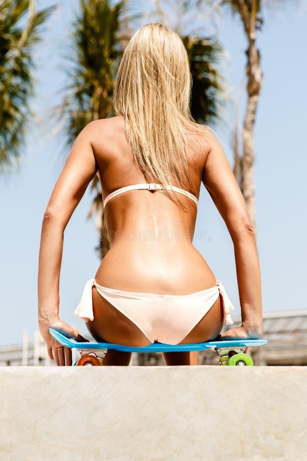 Seksowny suntanned damy obsiadanie na błękitnej cent desce w parku obrazy royalty free