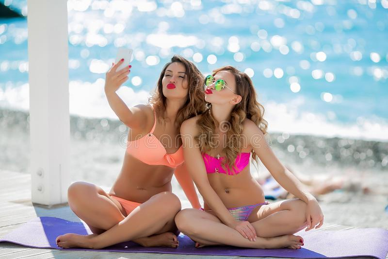 Seksueel meisje in een heldere bikini op een zonnig strand Bikini, rode lippen, blauwe overzees, gelooid meisje Twee vrienden heb stock afbeeldingen