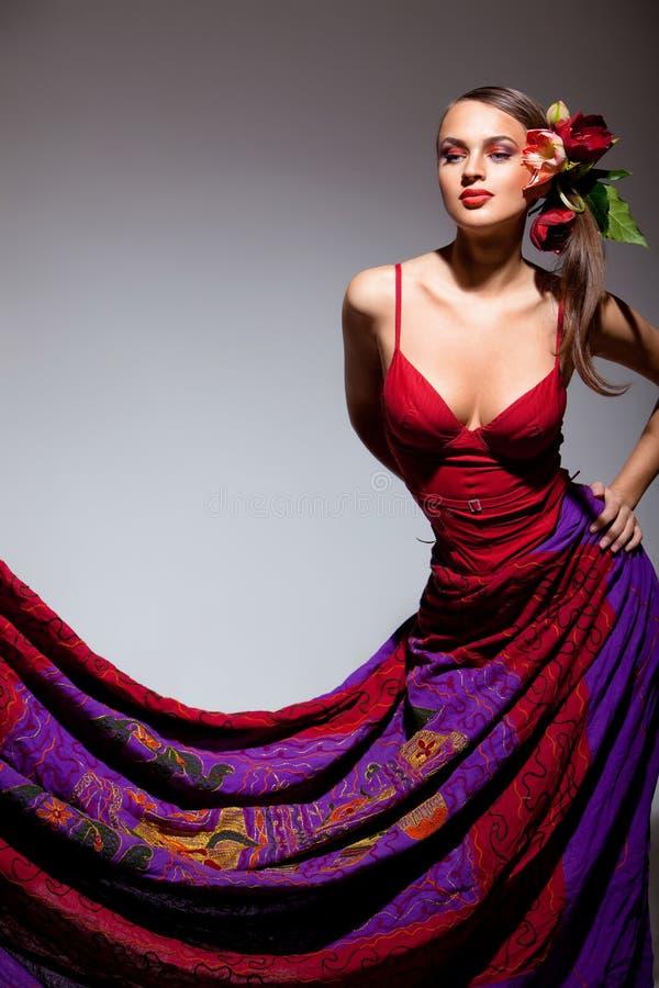 Seksueel meisje in rode kleding met bloemen in haar haar royalty-vrije stock fotografie