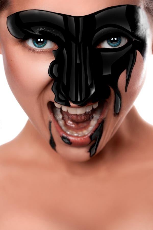 Seksueel wijfje met zwarte verf bij gezicht het gillen stock foto