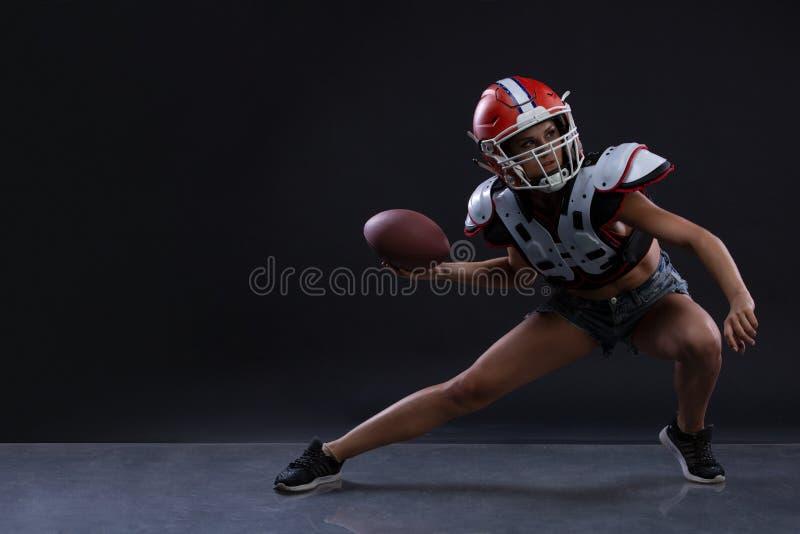 Seksuele sportieve vrouw die met rugbybal lopen en agressief bij zwarte achtergrond gillen Gendergelijkheid royalty-vrije stock fotografie