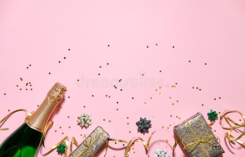 Sektflasche mit bunten Parteiausläufern und Geschenkbox auf rosa Hintergrund Einladungskartenmodell, Postkarte, Fahne lizenzfreie stockfotos