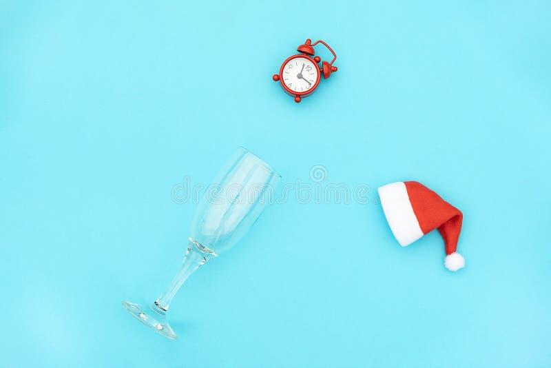 Sektkelch mit rotem Wecker in Sankt-Hut auf blauem Hintergrund Kreatives Konzept Weihnachts- oder des neuen Jahrestrinkende Zeit  stockfoto