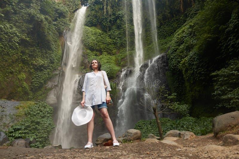 Sekumpul siklawa z beuatiful turystyczną dziewczyną w Bali, Indonezja obrazy royalty free