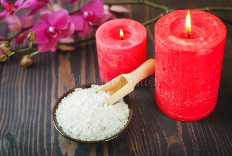 Sel, bougies et fleurs de bain de mer sur un fond en bois Le concept des procédures de station thermale images libres de droits