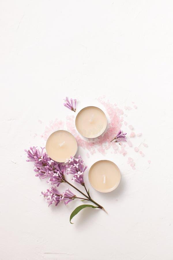 Sel, bougies et un brin de lilas pour l'aromatherapy sur un blanc images libres de droits