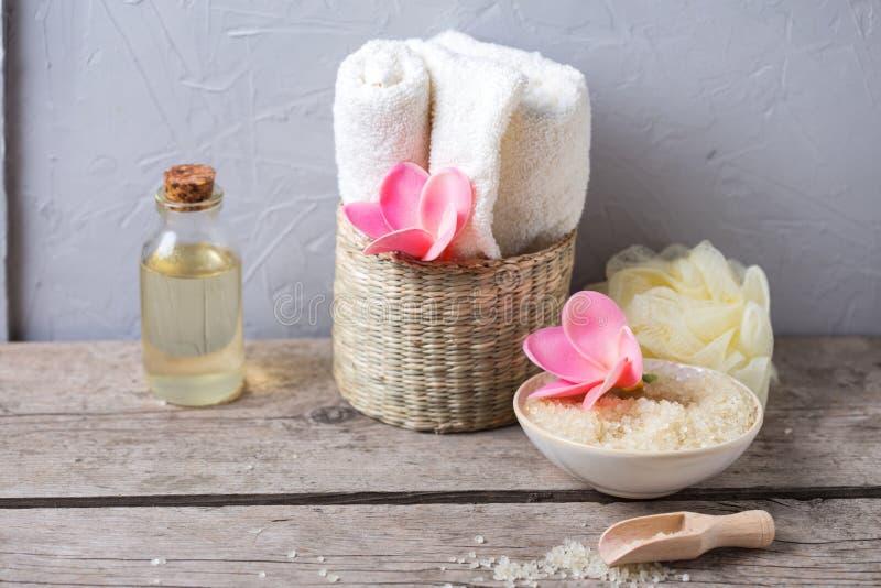 Sel de mer en cuvette, serviettes, bouteilles avec de l'huile d'arome et fleurs dessus photographie stock