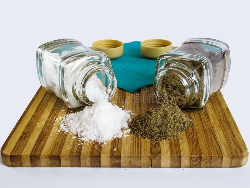 Sel et poivre dispersés des dispositifs trembleurs de sel en verre et des dispositifs trembleurs de poivre sur une planche à déco images libres de droits