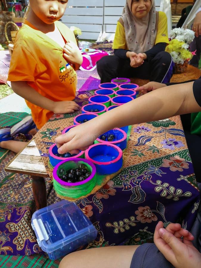 Selangor, Malaysia - Dec 8, 2019 : People playing congkak made from recycled items at the Majlis Perbandaran Kajang event in Taman. Tasik Cempaka, Bangi. Caring royalty free stock photography