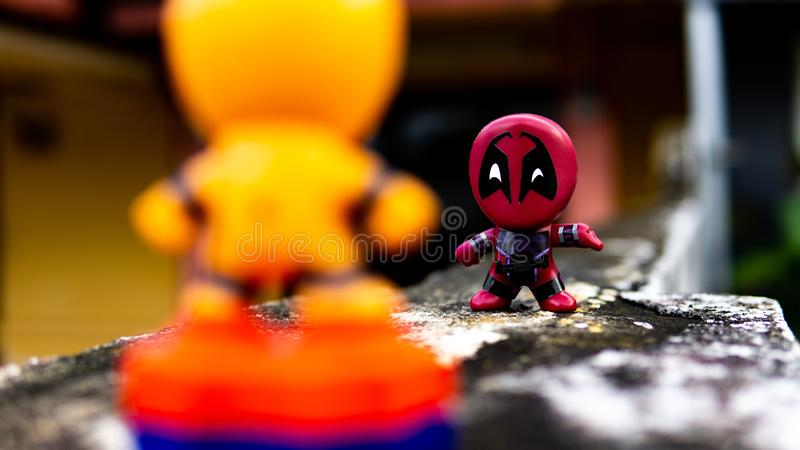 Two McDonald's toy Deadpool and orange spiderman having a final fight on the road. Selangor , Malaysia - March 28, 2019: Two McDonald's toy Deadpool and orange royalty free stock photography