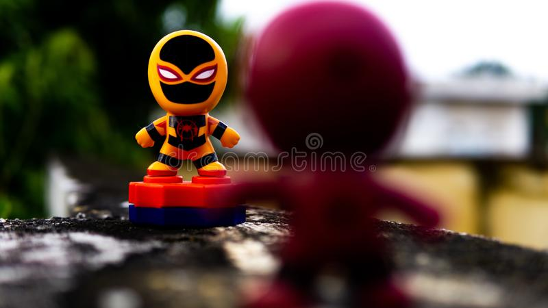 Two McDonald's toy Deadpool and orange spiderman having a final fight on the road. Selangor , Malaysia - March 28, 2019: Two McDonald's toy Deadpool and orange royalty free stock photos