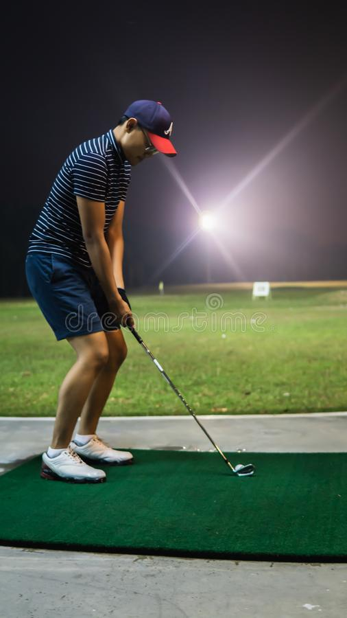 A man with a short pants swinging golf clubs at the driving range during the night royalty free stock images